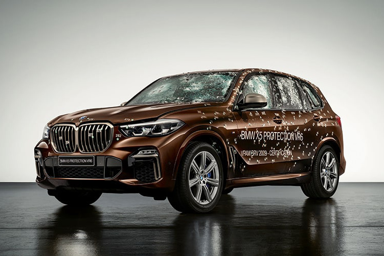 BMW X5 in Brown Metallic, covered in bullet holes, three-quarter front view, in front of a white wall