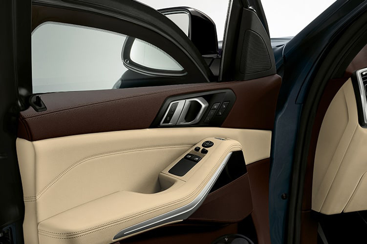Close-up of two-tone leather interior, light beige and dark brown, open driver's door
